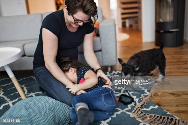 mother playing with daughter while sitting on carpet at home - tickling stock pictures, royalty-free photos & images