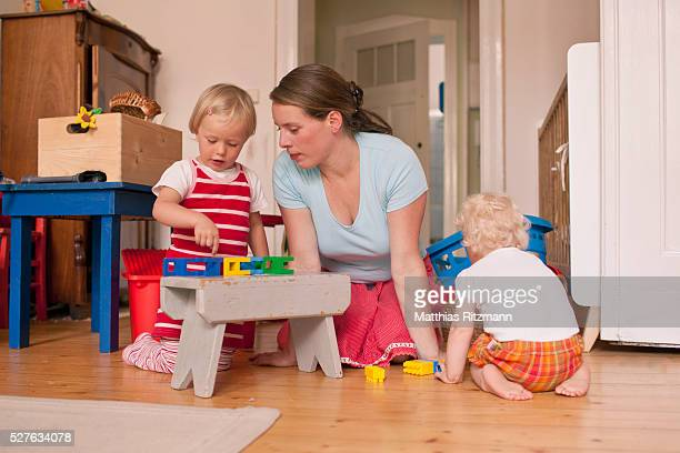 Mother playing with daughters (6-12 months,3-4)