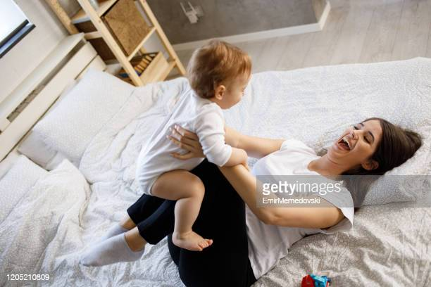 mother playing with her baby boy on bed - emir memedovski stock pictures, royalty-free photos & images