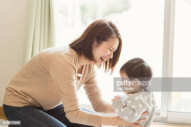 mother playing with her baby girl at home - asian baby stockfoto's en -beelden
