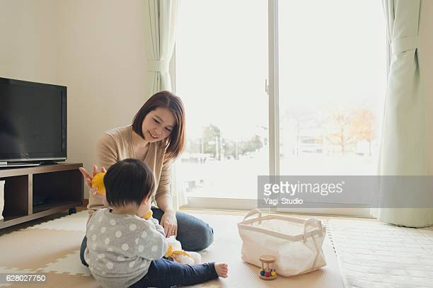 mother playing with her baby girl at home - シングルマザー ストックフォトと画像