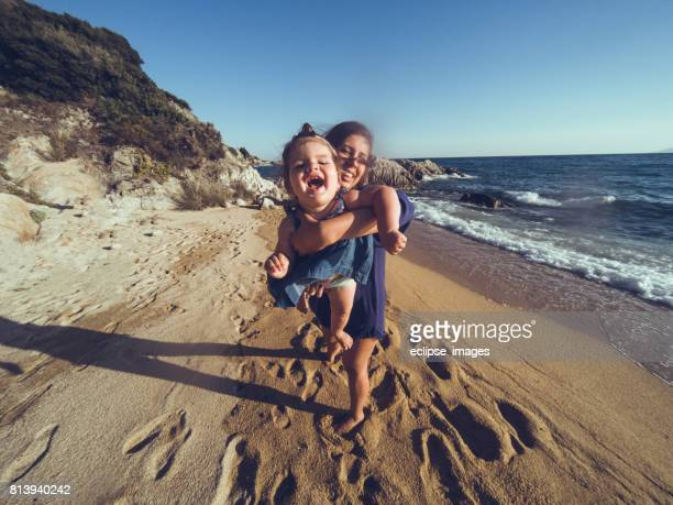 mother playing with her daughter on the beach at sunset - mothers day beach stock pictures, royalty-free photos & images