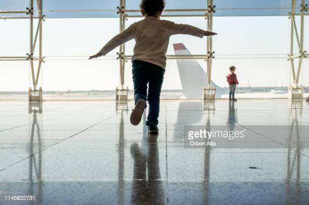 mother playing with her kids at the airport - kid in airport stock pictures, royalty-free photos & images