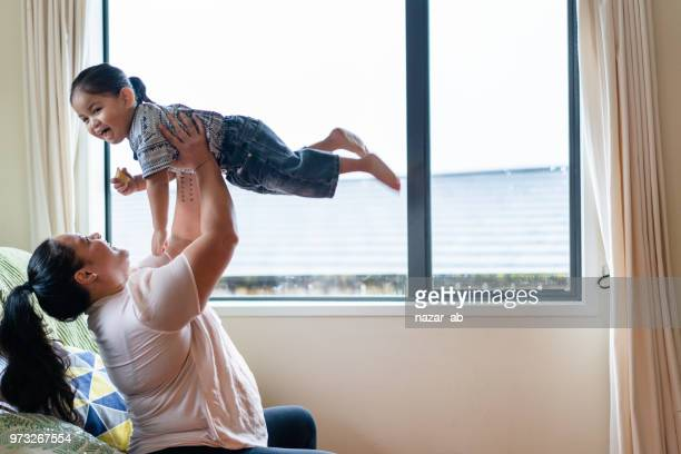 Mother playing with her son at home.