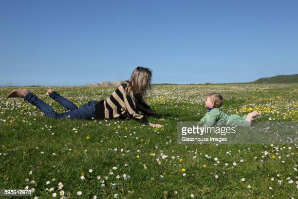 Mother Playing with Infant Child in Field of Wildflowers