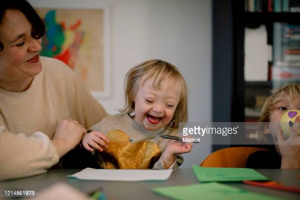 mother playing with smiling disabled daughter while sitting at home - intellectually disabled stock pictures, royalty-free photos & images