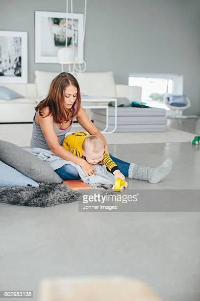 Mother playing with son in living room