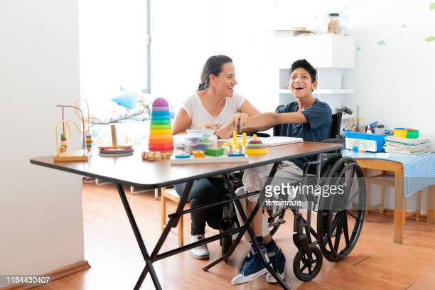 mother playing with son with cerebral palsy - physical disability stock pictures, royalty-free photos & images