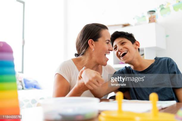 mother playing with son with cerebral palsy - body care stock pictures, royalty-free photos & images