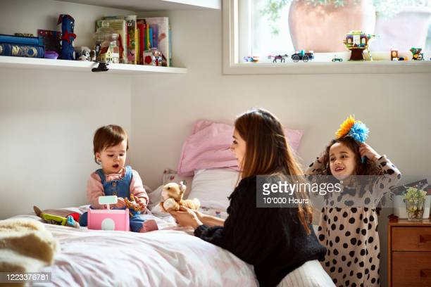 mother playing with two girls in bedroom - participant stock pictures, royalty-free photos & images