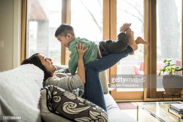 mother playing with young son (2 yrs) on couch at home - family playing stock pictures, royalty-free photos & images