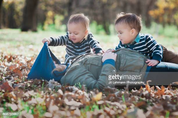 Mother plays 'Peek' with Fraternal Twins outside on an Autumn Day
