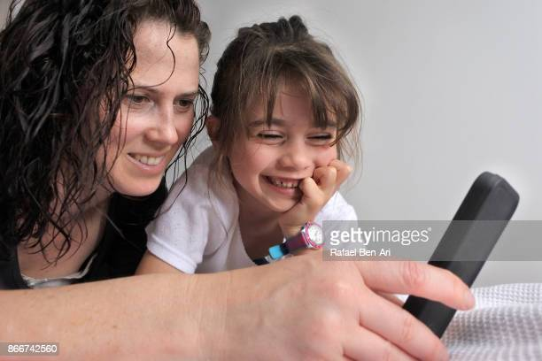 Mother plays together with her daughter on a mobile phone