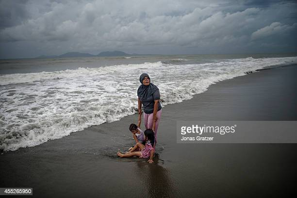 A mother plays with her child in the shallow water on the beach of Banda Aceh 10 years after it was struck by the deadly tsunami disaster The tsunami...