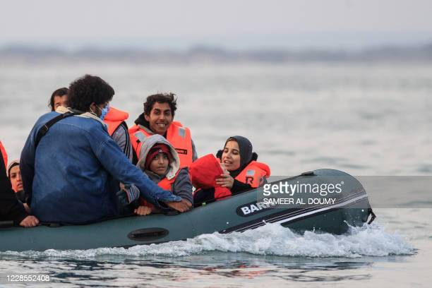 Mother plays with her kid in a dinghy as they illegally cross the English Channel from France to Britain on September 11, 2020. - The number of...
