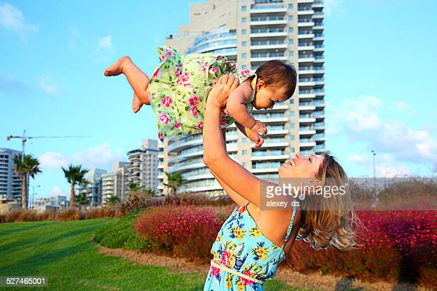 mother plays with her little daughter on sunset - human arm stock pictures, royalty-free photos & images