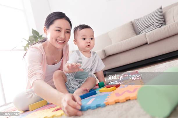 Mother plays with the baby sitting room