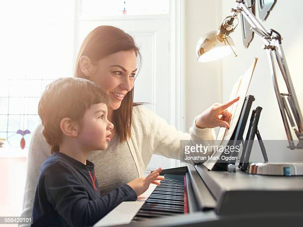 Mother pointing at sheet music to teach son to play piano at home