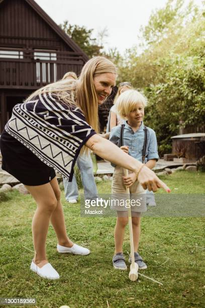 mother pointing while standing by son playing polo in front yard - polo stock pictures, royalty-free photos & images