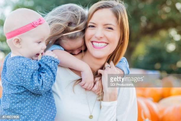 Mère pose pour portrait sincère avec filles en champ de citrouilles