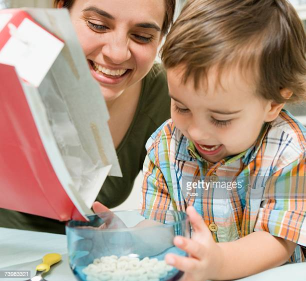 Mother pouring breakfast cereal for her child