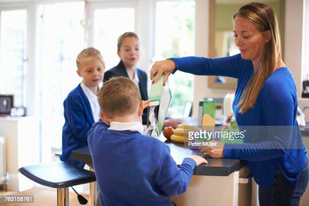 Mother pouring breakfast cereal for son in kitchen