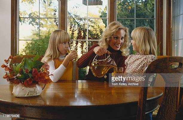 Mother pouring juice for daughter