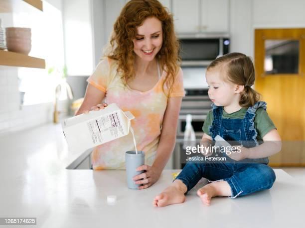 mother pouring milk for daughter (2-3) - milk carton - fotografias e filmes do acervo