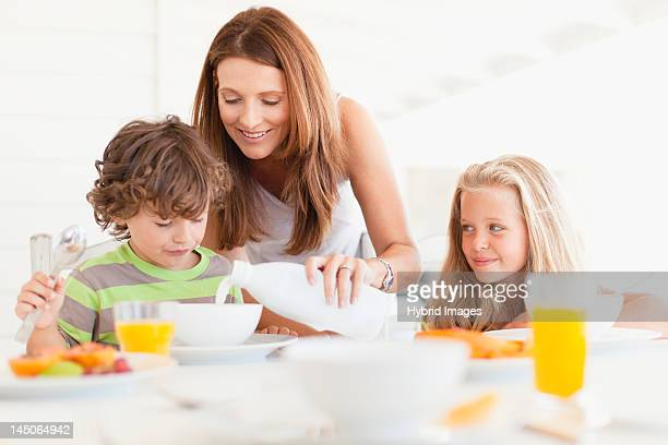 Mother pouring milk for son