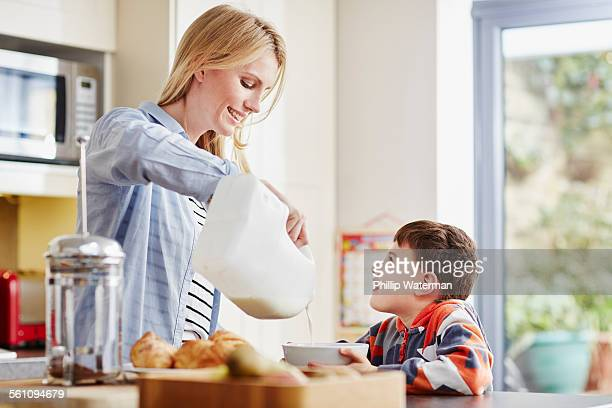Mother pouring milk into sons breakfast bowl