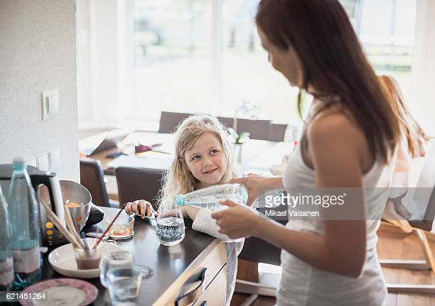 Mother pouring water for daughter in kitchen