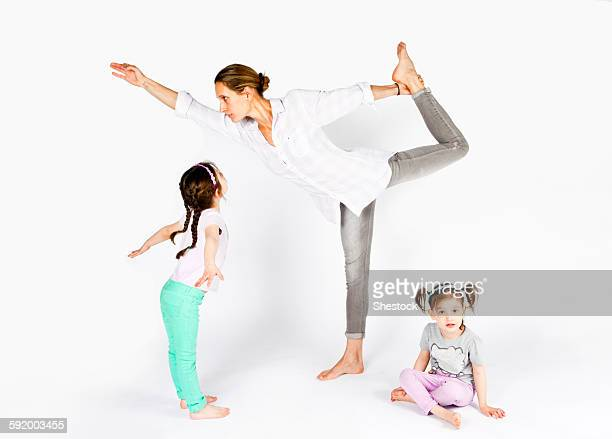 Mother practicing yoga with playful daughters
