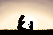 Mother Praying with her Young Child Outside at Sunset.