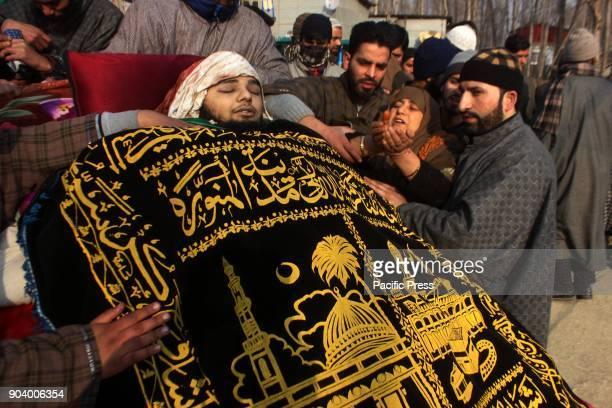 Mother prays near the body of a 16 year old Kashmiri rebel Farhan Ahmad Wani during funeral procession at Redwani village of kulgam District 60KM...