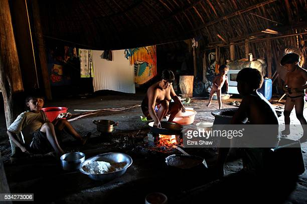 A mother prepares beiju a food made out of manioc for her children on May 6 in the village of Kamayura Brazil Manioc is harvested from the fields...