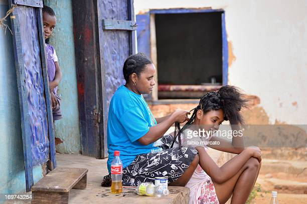 Mother prepares the braids for the daughter
