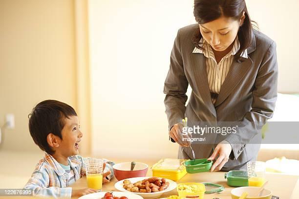mother preparing a lunchbox - accompagnement photos et images de collection