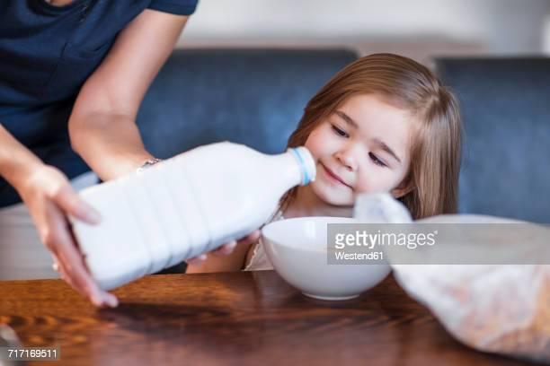 Mother preparing breakfast for her daughter