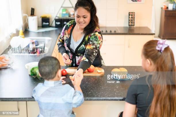 Mother preparing breakfast for kids.