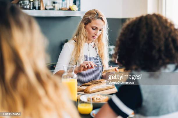 mother preparing breakfast in her kitchen - spreading stock pictures, royalty-free photos & images