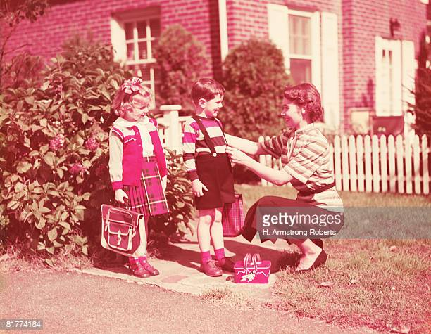 Mother preparing daughter and son to go to school with lunch boxes, books and bags. (Photo by H. Armstrong Roberts/Retrofile/Getty Images)