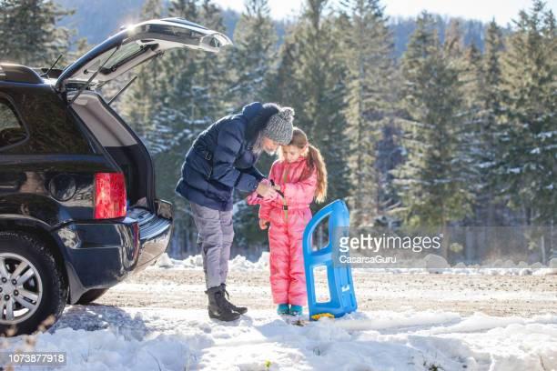 mother preparing daughter for tobogganing - tobogganing stock pictures, royalty-free photos & images