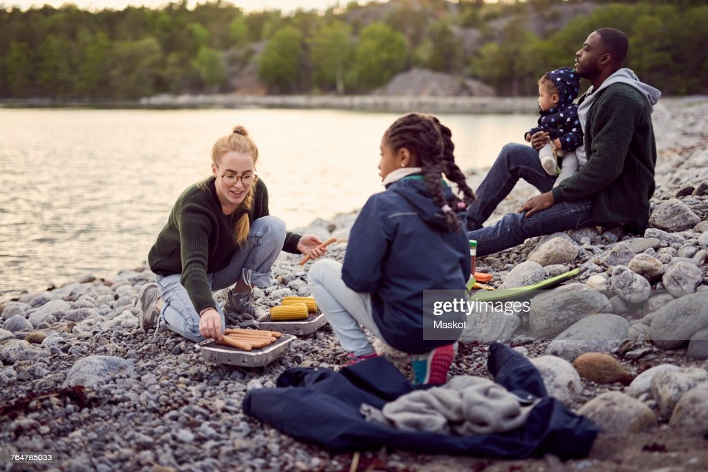 Mother preparing food on barbecue grill amidst family sitting on rocks at beach during camping : Stock Photo
