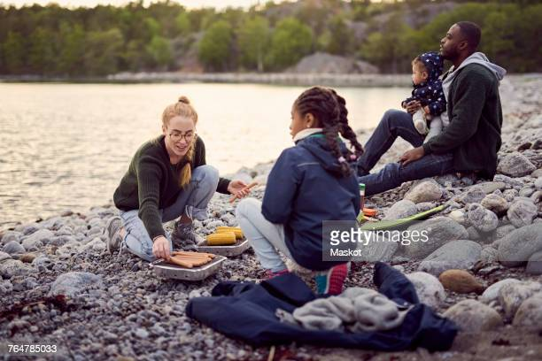 mother preparing food on barbecue grill amidst family sitting on rocks at beach during camping - black family dinner stock photos and pictures
