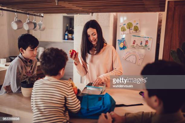 Mother preparing healthy food lunch boxes for children in kitchen