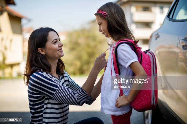 mother preparing her child for school in front of their house - life events stock pictures, royalty-free photos & images