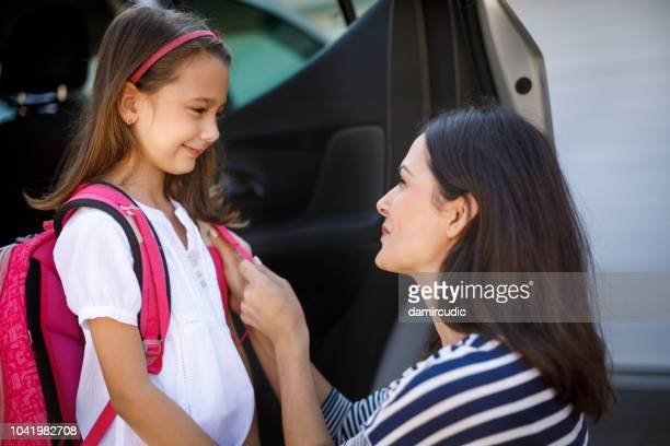 mother preparing her child for school in front of their house - open backpack stock pictures, royalty-free photos & images