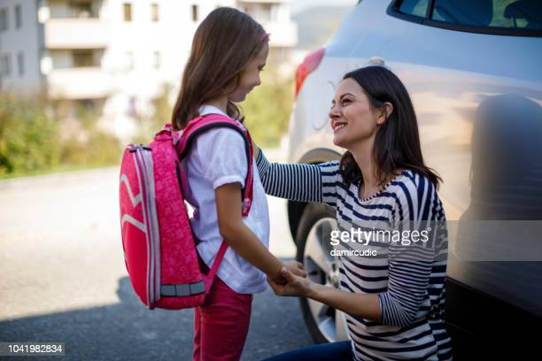 mother preparing her child for school in front of their house - parental leave stock pictures, royalty-free photos & images