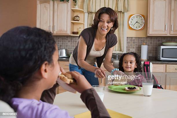 Mother preparing lunch for daughters at home