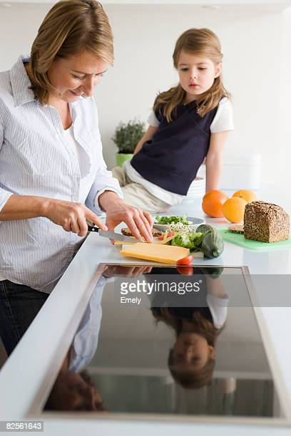mother preparing sandwich for daughter - northern european stock photos and pictures